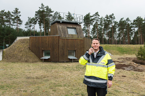 Dr. Kai Holtappesl in front of the observation bunker on the BAM Test Site at Horstwalde: he is in touch by mobile with colleagues who are preparing a steel container for a test series on the explosion stand.