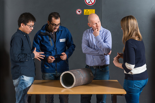 The team around Dr.-Ing. Jürgen Olbricht examines a piece of a power plant steam line (from left to right: Dong Wang, Dr.-Ing. Hamed Ravash, Dr.-Ing. Jürgen Olbricht and Maria Jürgens).