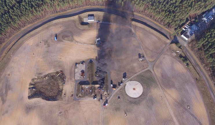 A bird's eye view of a fire test with a plume of smoke that is visible from a distance.