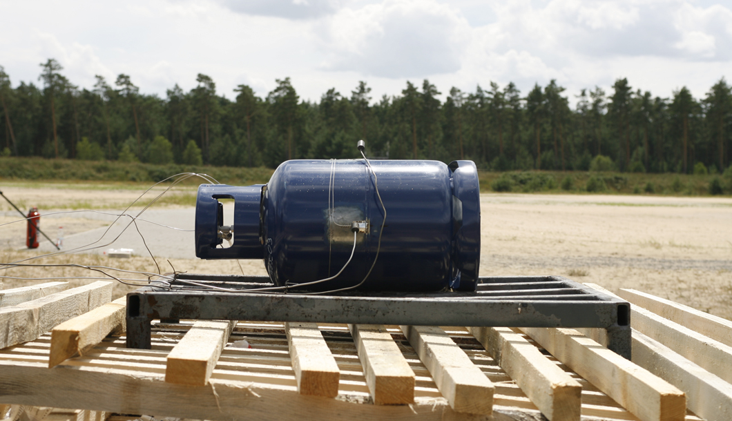 An 11 kg propane gas cylinder is being prepared for an underfiring test with wood.