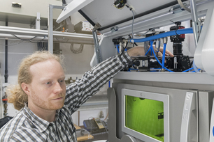 Dr Simon Altenburg adjusts the camera aperture on a laser beam melting device used for optical tomography.