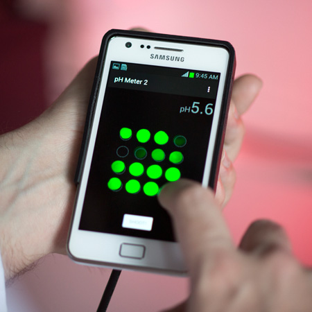 A BAM employee is holding a smartphone with a quick pH test in their hand.