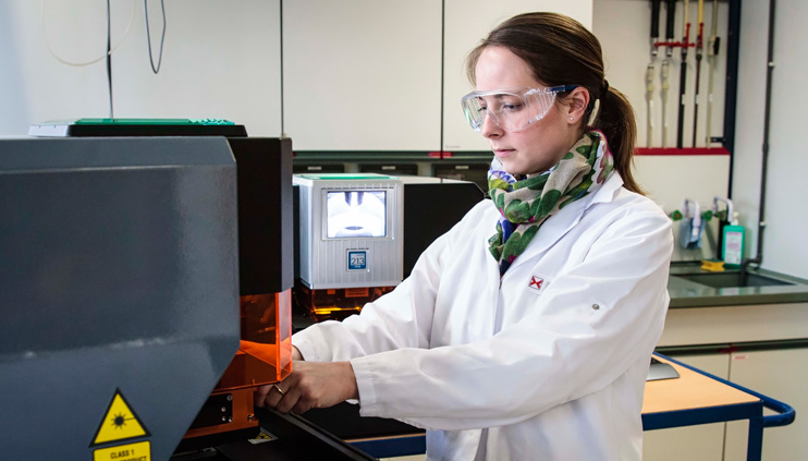 Dr. Larissa Müller places a cell sample under the laser of the element microscope.