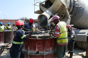 Working with ready-mixed concrete at a construction site in Tanzania