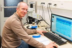 Dr. Dirk Bettge with a material sample under an optical microscope.