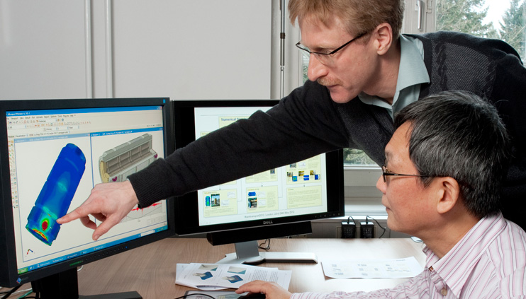 Dr. Holge Völzke (standing) and Dr. Linan Qiao assess the simulation of a container for highly radioactive waste.